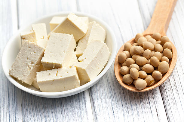 bowl of tofu and spoonful of soybeans on wood surface - tofoe stockfoto's en -beelden