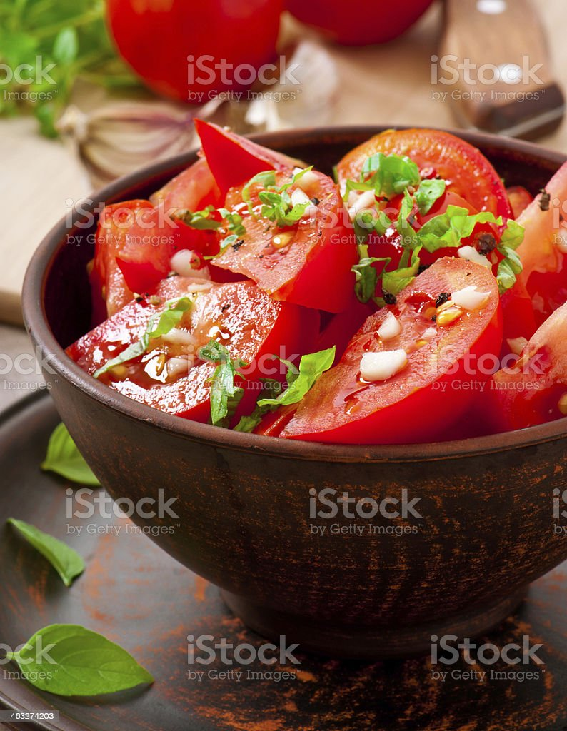 Bowl of tomato salad with basil, garlic and black pepper stock photo