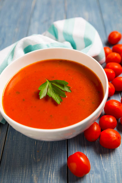 Bowl of tomato soup on blue surface with fresh tomatoes stock photo