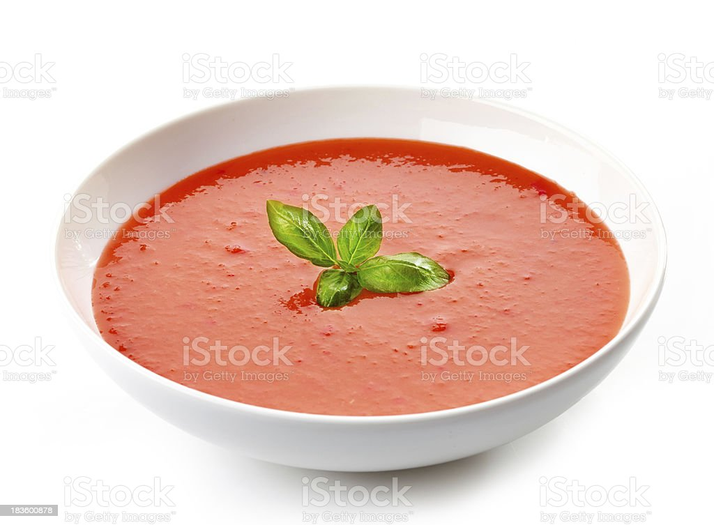 bowl of tomato soup with basil stock photo