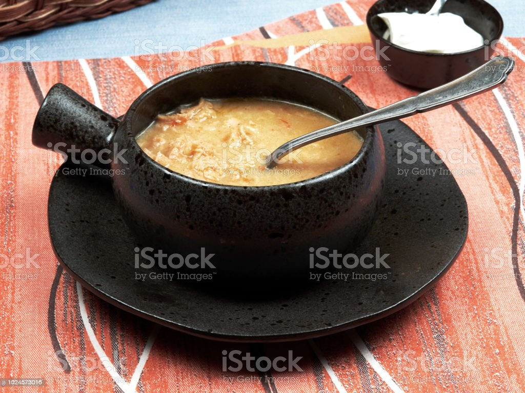 A bowl of tripe soup (Romanian: Ciorba de Burta) set on a red napkin placed on a blue tablecloth, served with extra cream and a basket of bread stock photo