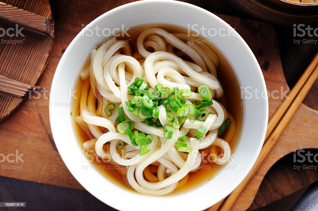 A bowl of udon noodles in the broth on a wooden board royalty-free stock photo
