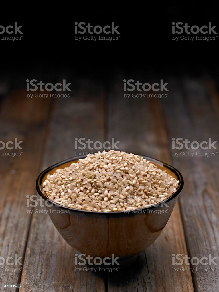 A bowl of uncooked brown rice on the table stock photo