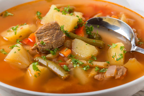 Bowl of vegetable beef soup with spoon stock photo