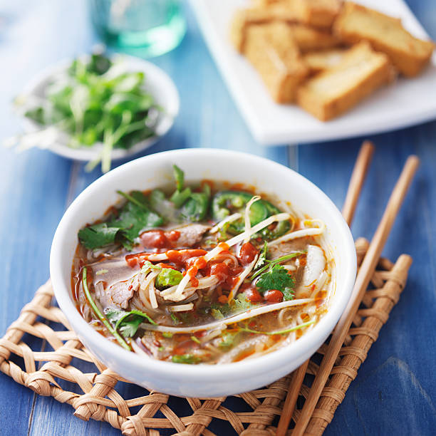 bowl of vietnamese Pho Tai beef soup bowl of vietnamese Pho Tai beef soup with spicy sriracha sauce sriracha tiger zoo stock pictures, royalty-free photos & images