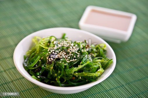 Wakame seaweed salad with nut sauce, garnished with sesame seeds and red chili pepper