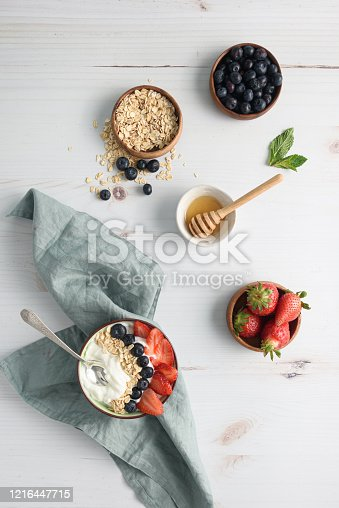 Bowl of yogurt with berries and oatmeal on table