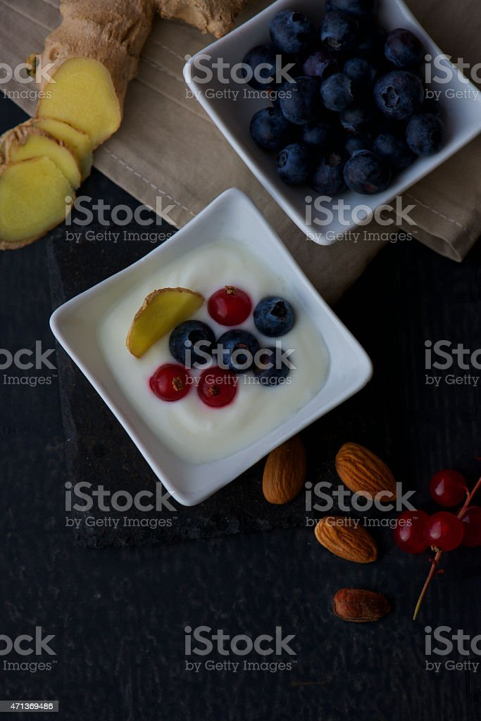 bowl of yogurt with blueberries ginger currant almonds from above stock photo
