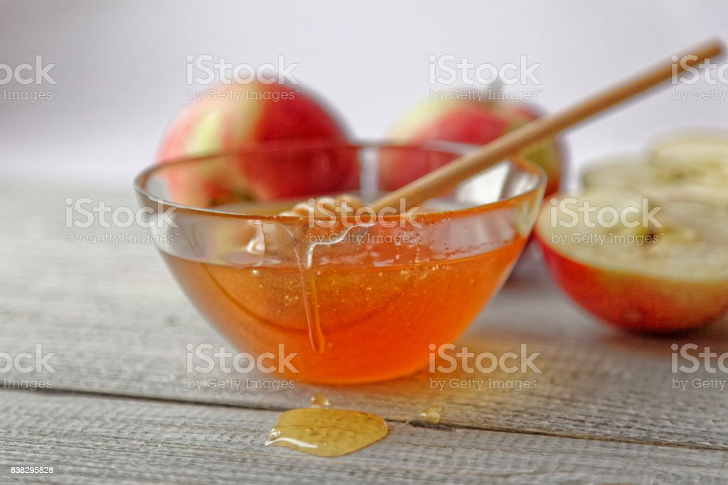 Bowl rustic honey and apples on wooden table. Traditional celebration food for the Jewish New Year. Concept Rosh Hashana. stock photo