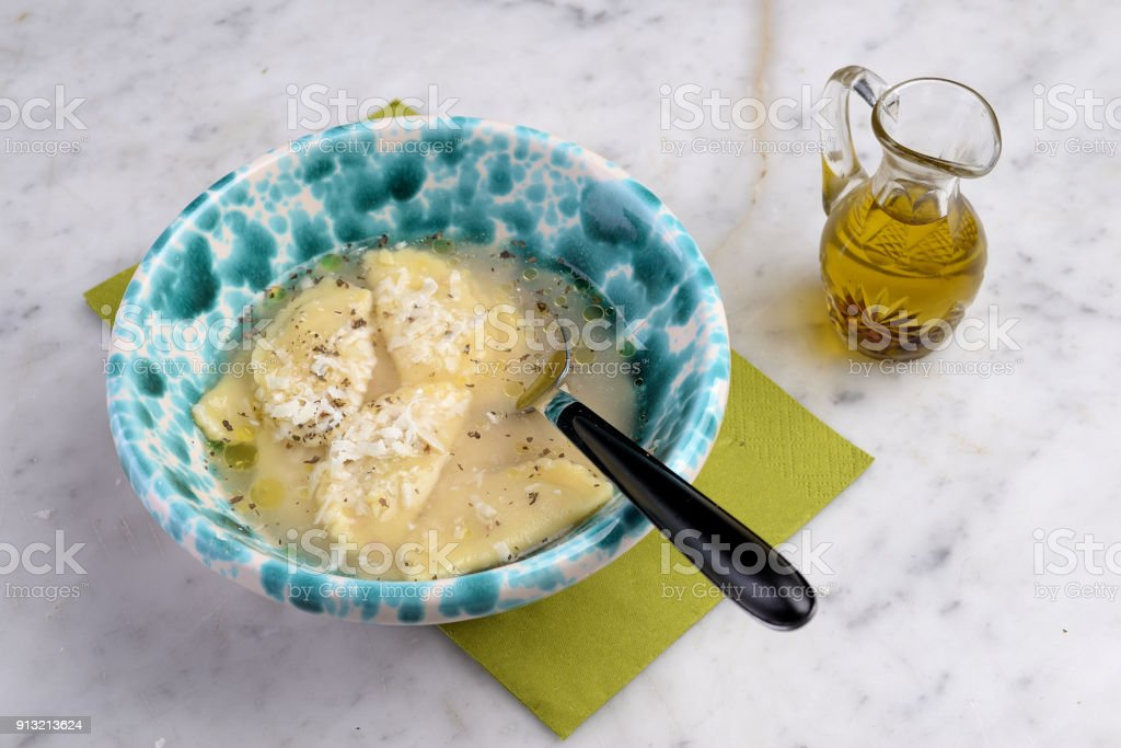Bowl with agnolotti pasta in broth stock photo
