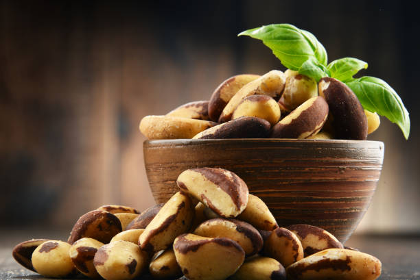 Bowl with Brazil nuts on wooden table stock photo