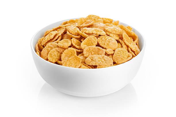 tazón con copos de maíz aislado sobre un fondo blanco. - corn flakes fotografías e imágenes de stock