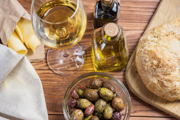 Bowl with different kind of olives, glass of wine, cheese and  fresh bread ciabatta on the wooden table. stock photo