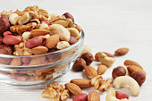 bowl with different mixed nuts on a white table