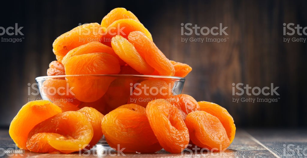 Schale mit getrockneten Aprikosen auf Holztisch – Foto