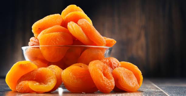 Bol avec des abricots séchés sur table en bois - Photo