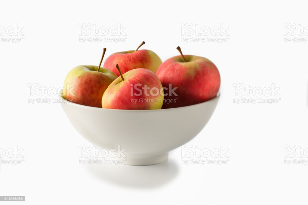 Bowl with four apples on white stock photo