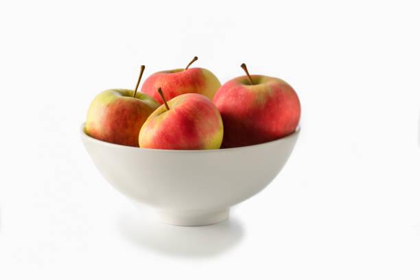 schale mit vier äpfel auf weiß - obstkorb stock-fotos und bilder