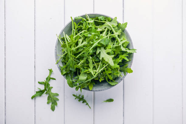 Bowl with fresh green salad arugula rucola Bowl with fresh green salad arugula rucola on a wooden Black or White background arugula stock pictures, royalty-free photos & images