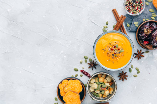 Bowl with fresh homemade carrot pumpkin soup and spices. stock photo