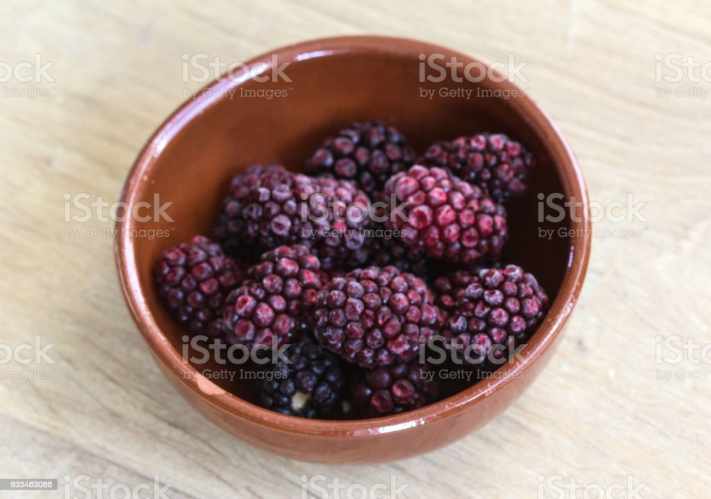 Bowl with Frozen blackberries on wooden background in kitchen stock photo