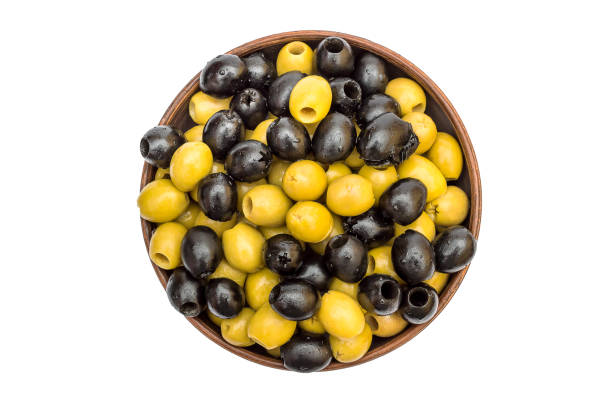 schale mit grünen und schwarzen oliven auf weiß. ansicht von oben. - schwarze olive stock-fotos und bilder