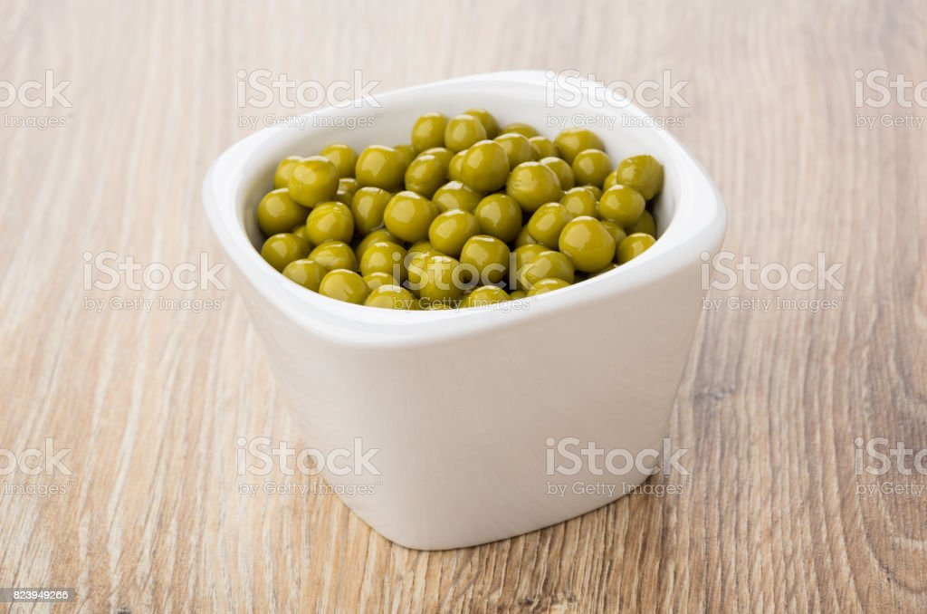 Bowl with green peas on table stock photo