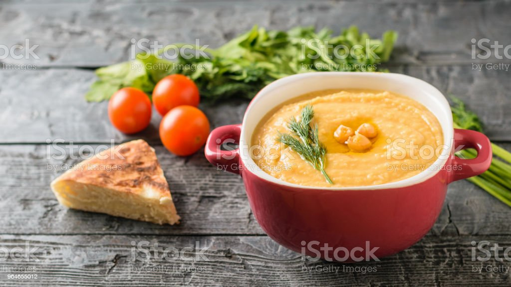 Bowl with hummus, parsley, tomatoes, herbs and lemon on the rustic table. royalty-free stock photo