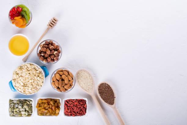 schale mit zutaten zum kochen hausgemachtem müsli auf weißem hintergrund. gesunden snak. flache lay - haferflocken rosinen stock-fotos und bilder