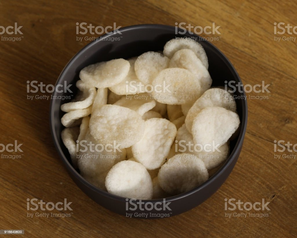 Bowl with Krupuk on wooden background stock photo