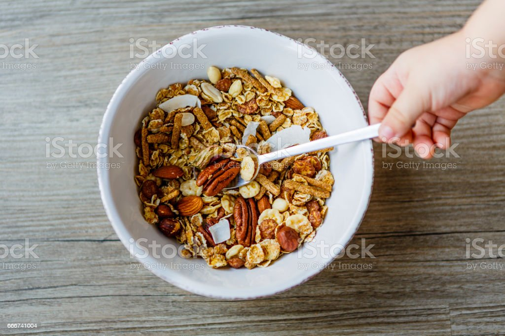 bowl with muesli and spoon on the wooden table prepared for healthy breakfast, child hand foto stock royalty-free