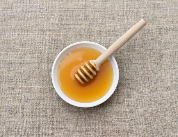 Schüssel mit Bio-Honig und Holzeimer Honig auf natürlichem Textilen – Foto