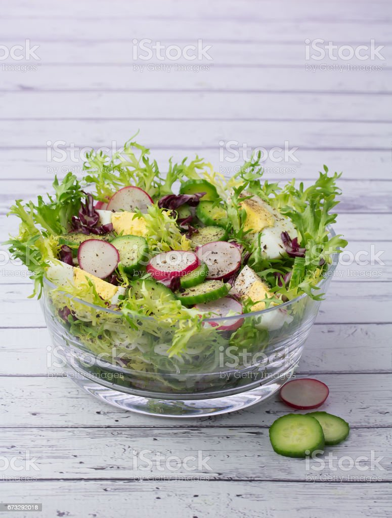 Bowl with organic salad on wooden background royalty-free stock photo
