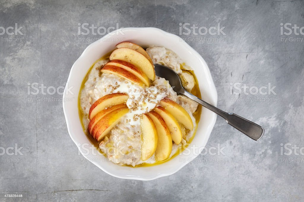 Bowl with porridge, apples, banana and sesame seeds stock photo