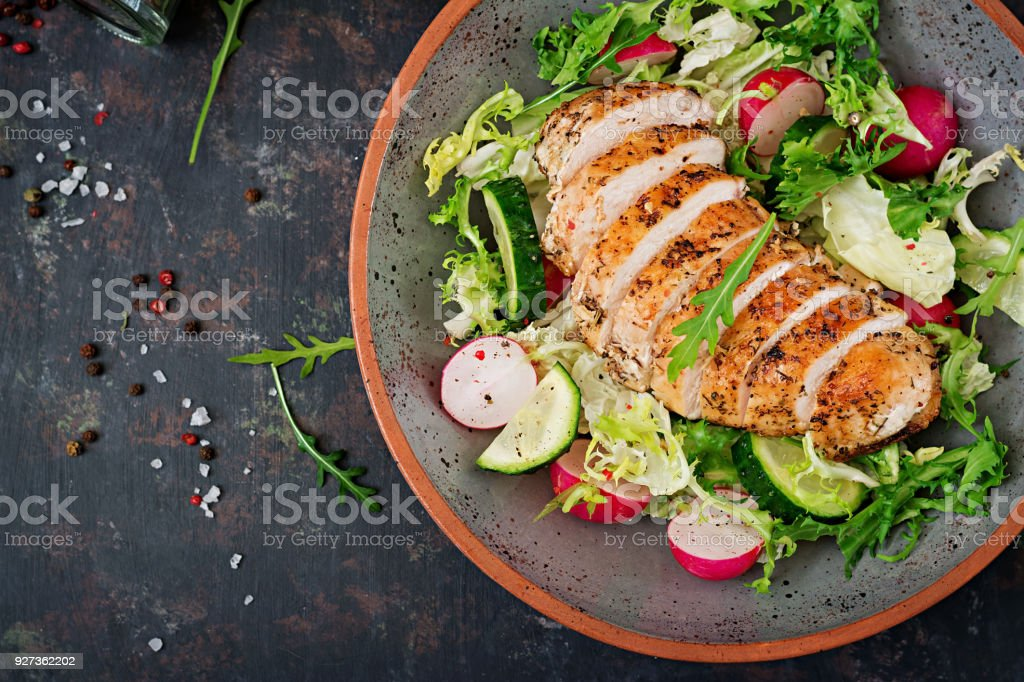Bowl with salad of fresh vegetables and baked chicken breast on a dark background. Proper nutrition. Dietary menu. Flat lay. Top view - Royalty-free Appetizer Stock Photo