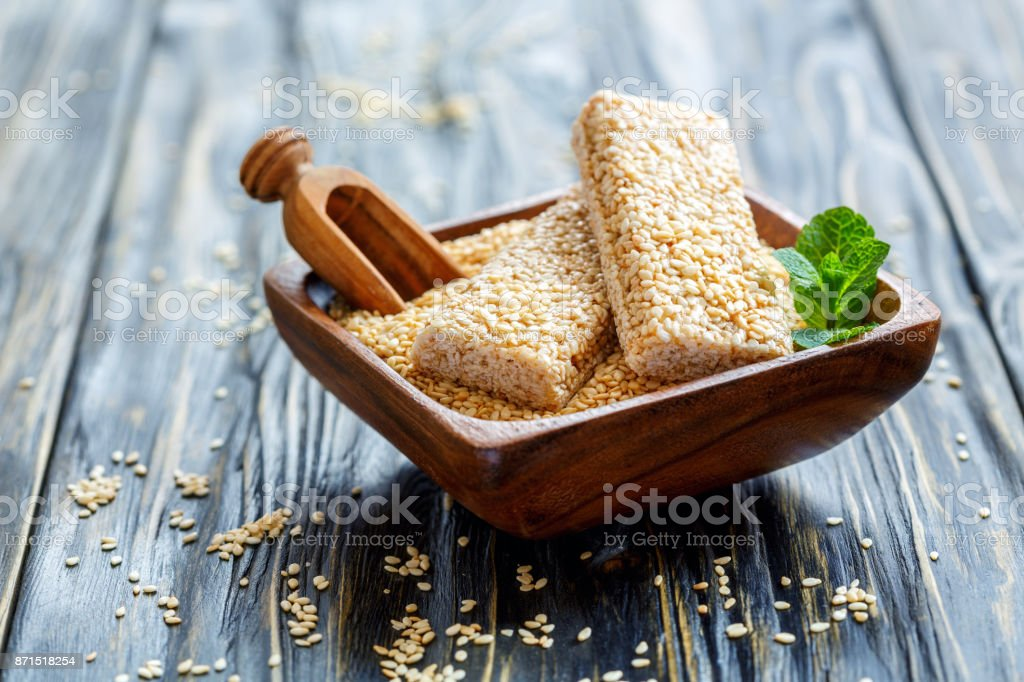 Bowl with sesame bars and a wooden scoop. stock photo