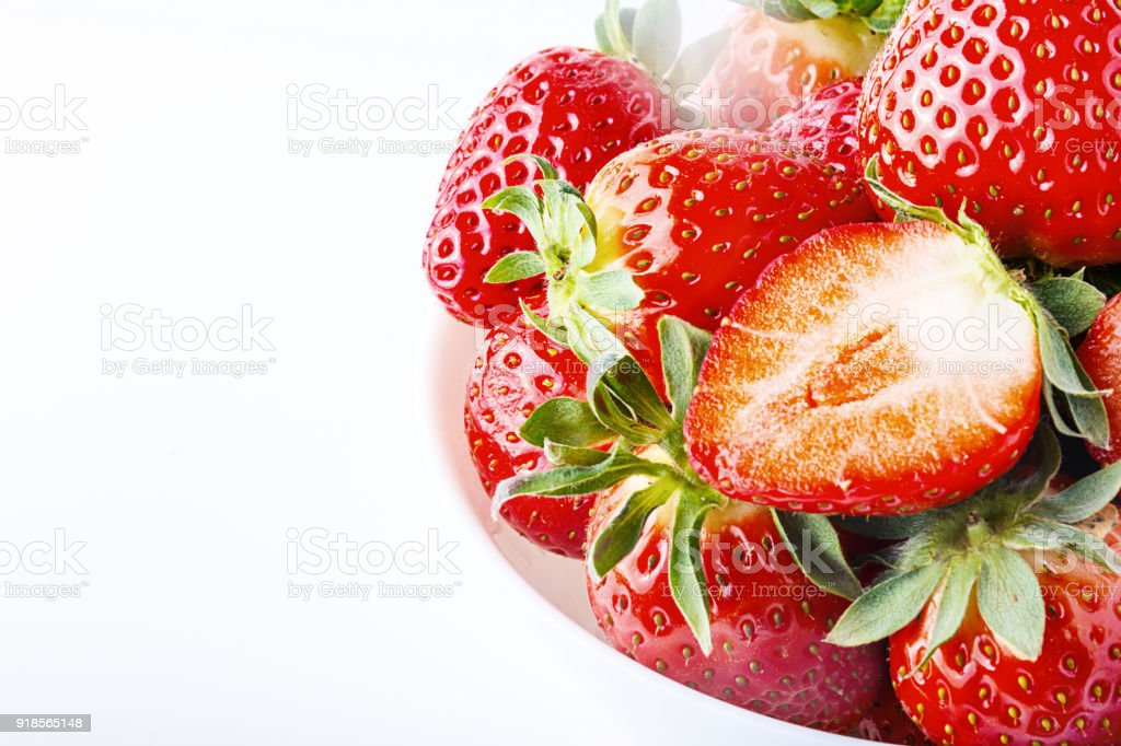 Bowl with strawberries isolated on white background. Ripe strawberries close-up stock photo