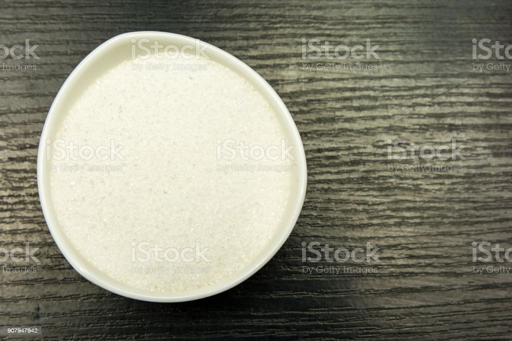 Bowl with white sugar. View from above. stock photo