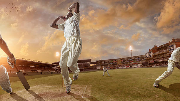 bowler delivering a fast ball during a cricket game - cricket stock photos and pictures