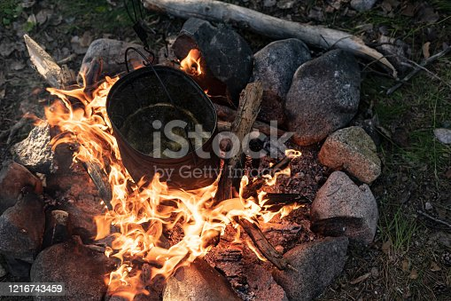 Bowler hat, with dinner being prepared, hangs over a campfire on a summer evening. Top view.