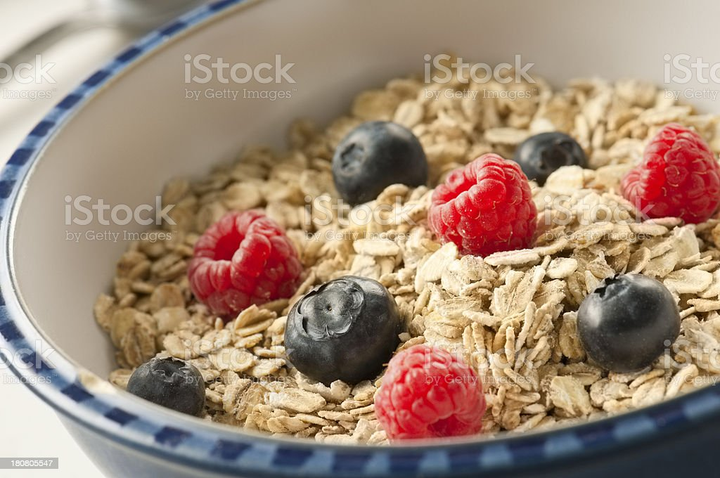 Bowlful of rolled oats with blueberries and raspberries stock photo