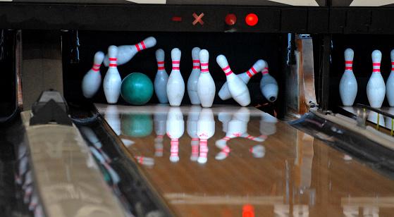 Bowling ball smacks a set of pins at a bowling alley.
