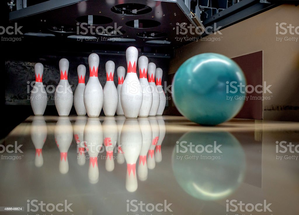 Bowling ball about to hit the pins on the alley