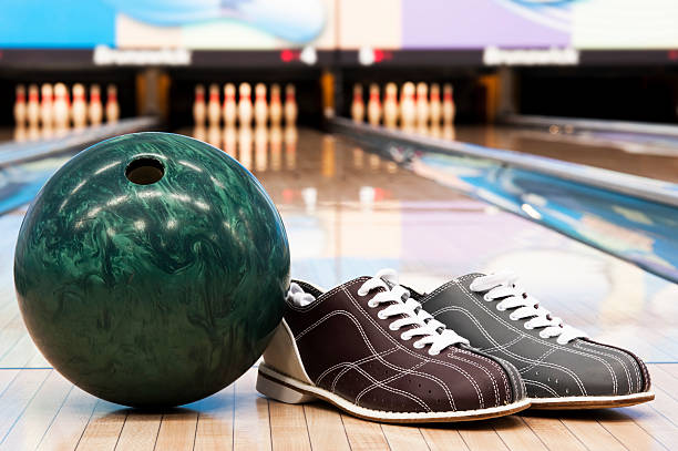 Bowling ball and shoes in bowling alley with background pins stock photo