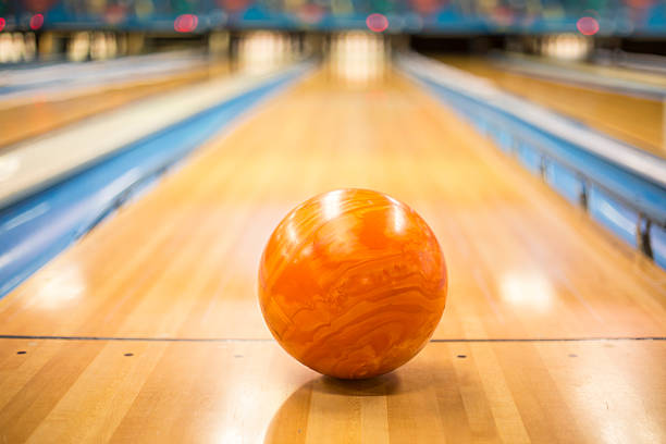 Bowling ball sitting in a colorful bowling alley lane stock photo