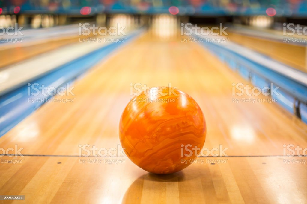 Close up view of an orange Bowling ball sitting in a colorful bowling...