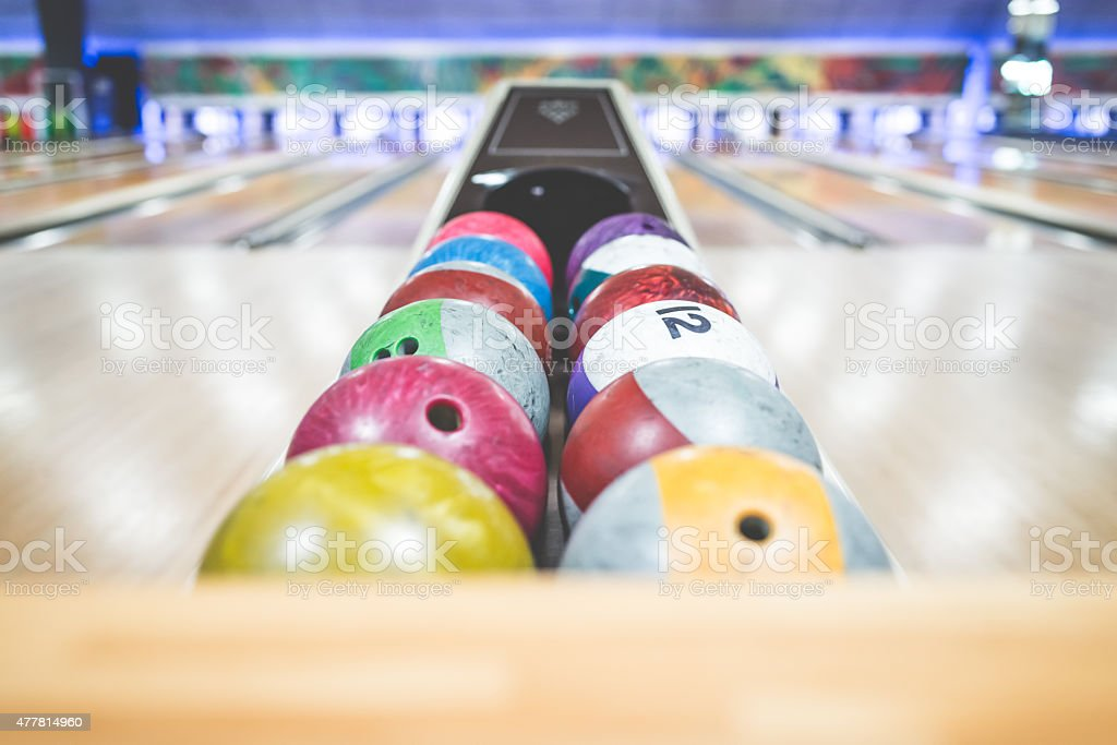 Bowling balls watihing to be thrown on the alley