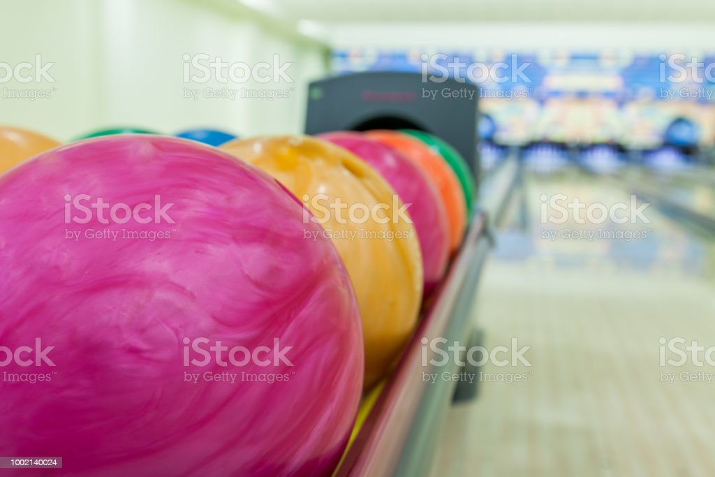 A lot of bowling balls standing on the shelf in bowling sport center