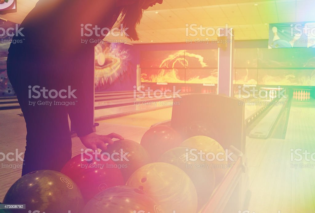 girl takes a Ball from the stand for bowling balls