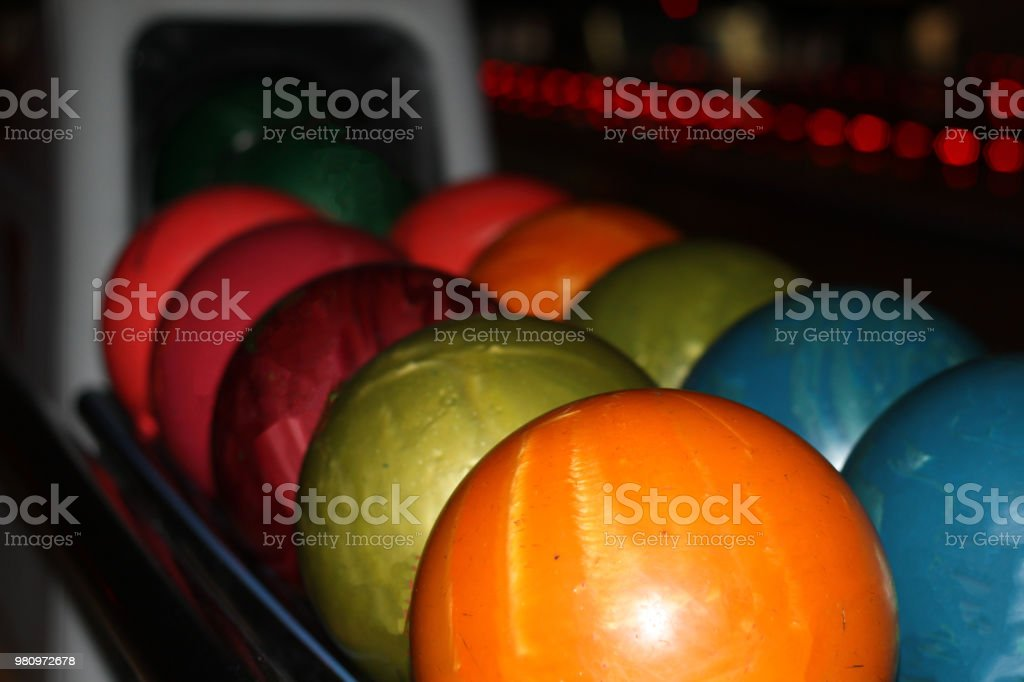 Multicolored bowling balls of different weight ready for the game
